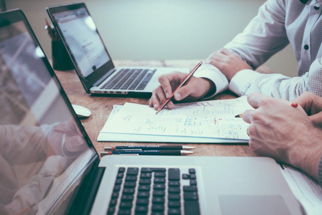 Mennesker som jobber foran en data