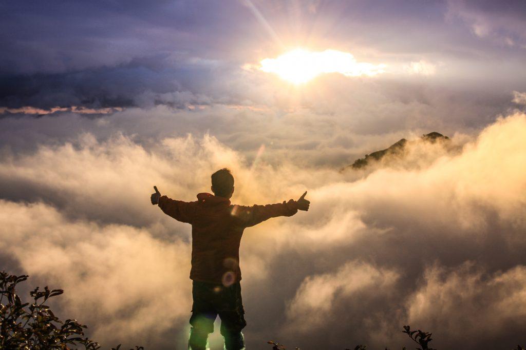 Glad mann som ser utover fjell